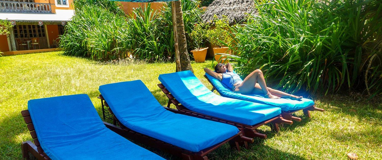 Sunbathing in private boutique hotel garden facing Diani Beach